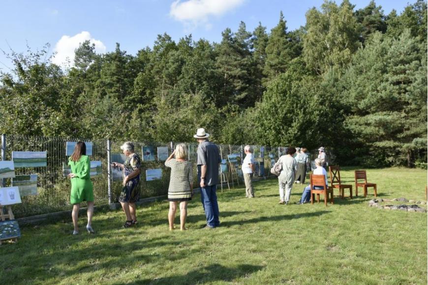 uczestnicy wernisażu oglądają prace zawieszone wśród zielenie