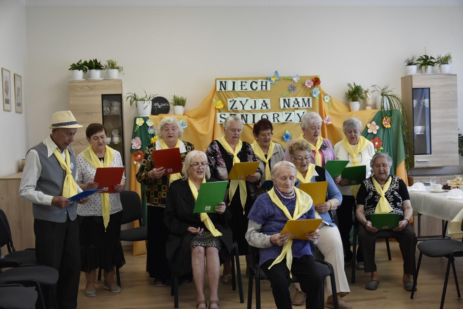 grupa seniorów w żółtych chustkach śpiewa piosenki