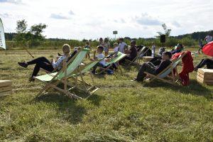 Miniatura zdjęcia: Ludzie siedzący na leżakach oglądający film w plenerze