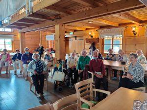 Miniatura zdjęcia: seniorzy w drewnianym budynku
