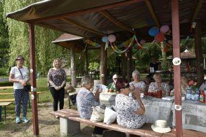 Miniatura zdjęcia: grupa seniorów siedzą przy stole w śród zieleni